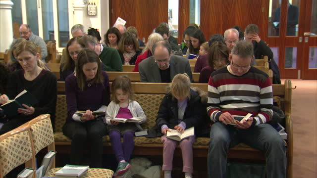 interior shots of the congregation of emmanuel church in wimbledon sat in pews as the minister leads them in prayer on january 10 2016 in london... - minister clergy stock videos and b-roll footage