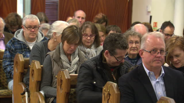 interior shots of the congregation of emmanuel church in wimbledon sat in pews as the minister leads them in prayer on january 10, 2016 in london,... - congregation stock videos & royalty-free footage