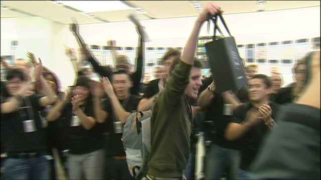 interior shots of the first apple iphone customers with their new iphones in bags at the apple store proudly walking as apple store staff cheer them - 2007 stock videos & royalty-free footage
