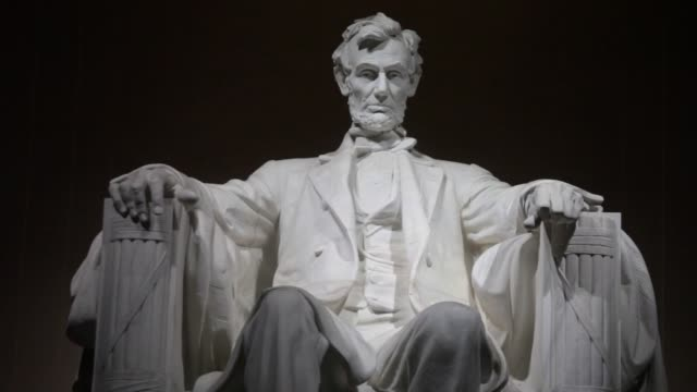 vidéos et rushes de interior shots of the lincoln memorial statue against a pitch black background after sunset in washington dc tourists and visitors' silhouettes... - lincoln memorial
