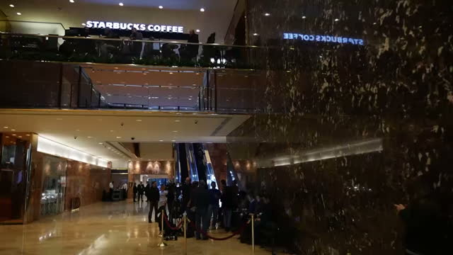 Interior shots of the lobby area of Trump Tower with its gold plated escalators a branch of Starbucks the Trump Bar and a number of security guards...