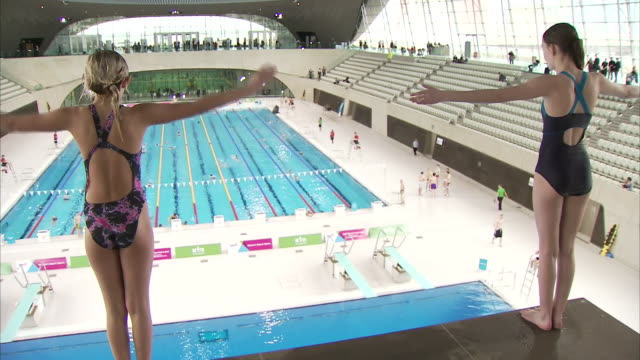 interior shots of the london aquatics centre in startford. kids swimming and jumping off the diving boards shot on 28th february 2014 in london - swimming pool stock videos & royalty-free footage