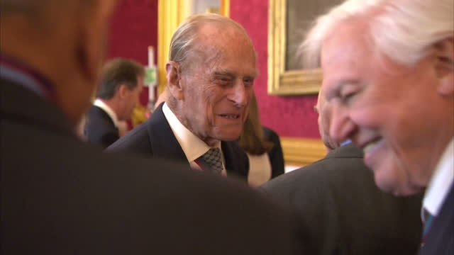 Interior shots of the Queen and Duke of Edinburgh speaking to guests at a reception for members of the Order of Merit at St James' Palace including...