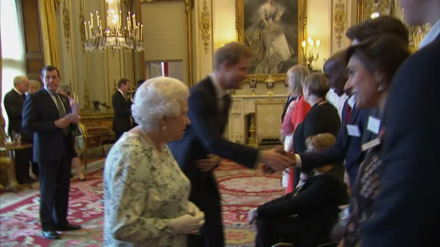 interior shots of the queen and prince harry speaking to guests at a reception for the 2017 queen's young leaders awards including sir mo farah liam... - 2017 stock-videos und b-roll-filmmaterial