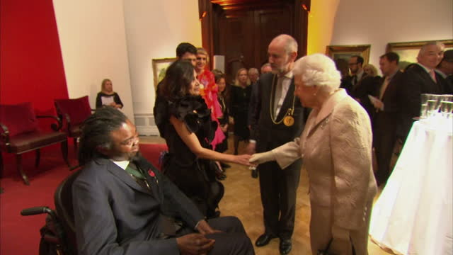 vídeos de stock e filmes b-roll de interior shots of the queen greeting guests including yinka shonibare and grayson perry at a reception at the royal academy of arts. >> on october... - royal academy of arts