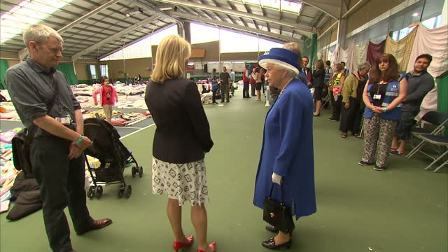 vídeos de stock, filmes e b-roll de interior shots of the queen inspecting charity aid donations for victims of the grenfell tower blaze and meeting charity workers and red cross staff... - 2017