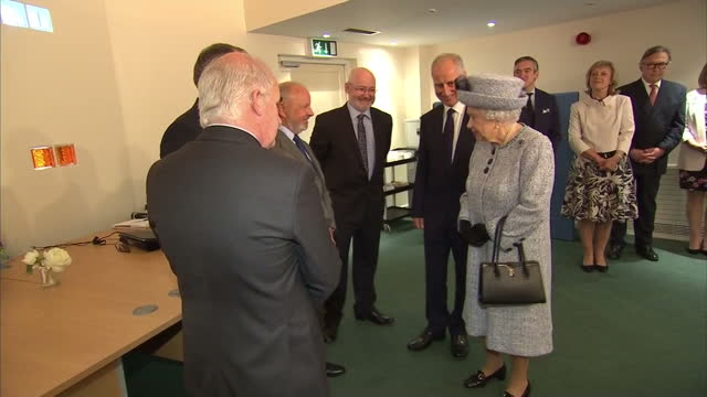 vídeos de stock, filmes e b-roll de interior shots of the queen meeting trustees and staff during a visit to sue ryder dee view court and signing a photograph after placing a letter in... - 2017