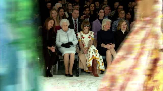 Interior shots of the Queen watching a runway show during a visit to London Fashion Week sitting between Professor Caroline Rush Chief Executive of...