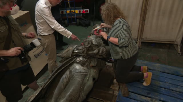 interior shots of the recoved statue of edward colston covered in graffiti with a restorer attending to it prior to its removal to a museum on 17... - removing stock videos & royalty-free footage