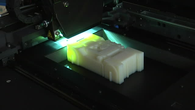 Interior shots of time lapse of laser printing machine making model car with green laser passing over it numerous times as it builds up the layers...