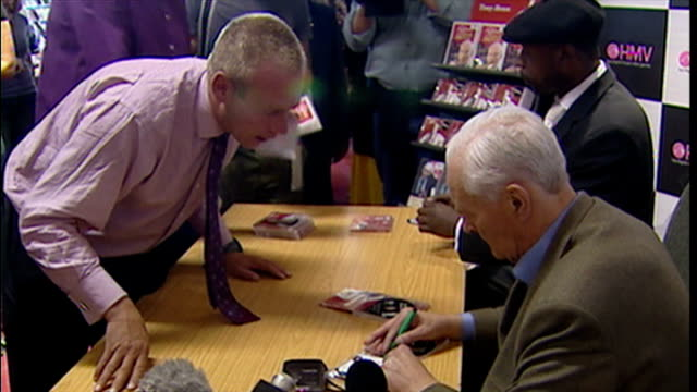 vidéos et rushes de interior shots of tony benn former mp signing cd's and dvd's with his autographs as people ring items to him to be signed - autographe