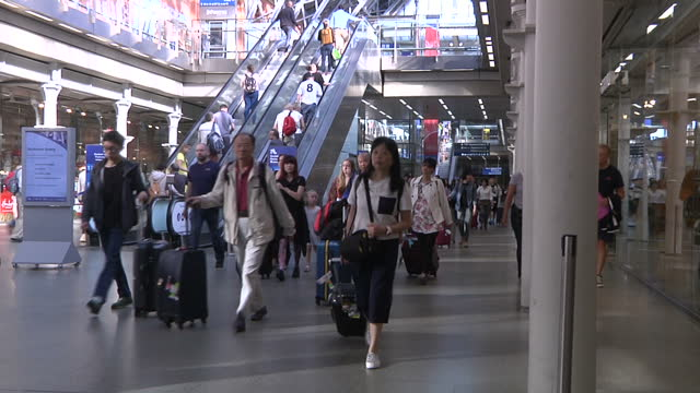 Interior shots of travellers walking around St Pancras International Train Station and people queueing up at Eurostar Departures line at St Pancras...