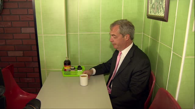 vídeos de stock, filmes e b-roll de interior shots of ukip leader nigel farage entering a pie and mash shop and posing for photos with a cup of tea on may 23, 2016 in dagenham, england. - pie humano