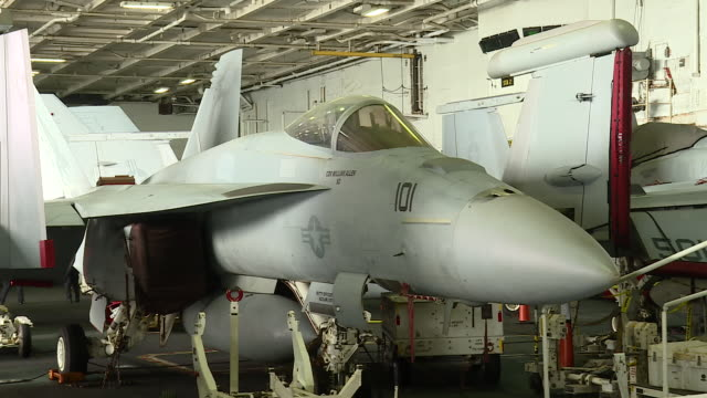 stockvideo's en b-roll-footage met interior shots of us navy fighter jets, helicopters and reconnaissance aircraft in hangar on board the uss abraham lincoln with maintanence staff... - oorlogsschip
