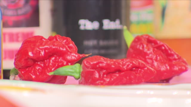 interior shots of various hot sauce bottles fresh chilli peppers dried chillie peppers on 15 april 2018 in uxbridge london - chilli con carne video stock e b–roll