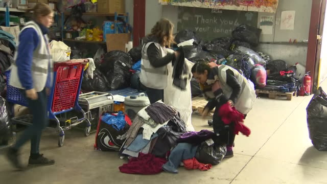 vidéos et rushes de interior shots of volunteers of the care4calais charity surrounded by piles of clothes and packing the clothes to give to refugees on 1 january 2019... - donner