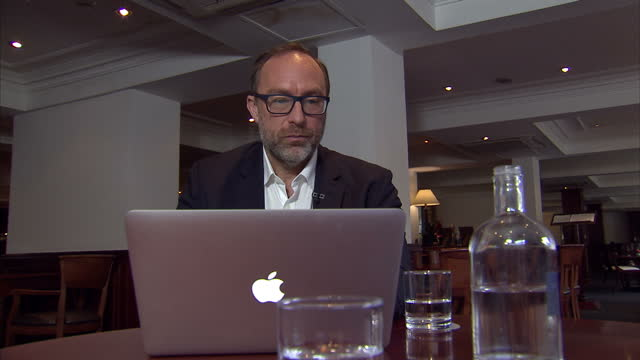 Interior shots of Wikipedia and Wikitribune founder Jimmy Wales sitting in an empty coffee bar or restaurant working at his Macbook laptop and...