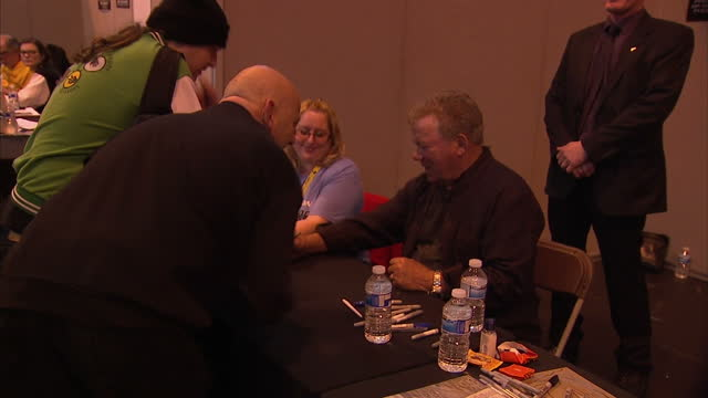 interior shots of william shatner signing autographs, and crowds of star trek fans queueing to have posters and other memorabilia signed.>> on... - william shatner stock videos & royalty-free footage