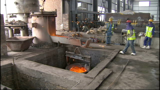 interior shots of workers in a large steelworks pouring hot molten metal from huge vats into molds and down chutes on july 7 2008 in beijing china - bottich stock-videos und b-roll-filmmaterial
