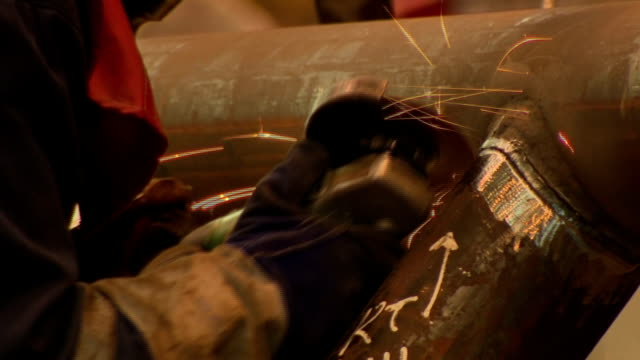 vídeos de stock, filmes e b-roll de interior shots of workers using angle grinders and welding equipment working on a metal structure inside an assembly hall at a fabrication and... - produto interno bruto