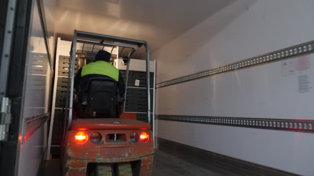 interior shots of workers using fork lifts to move boxes of packaged fruit and load them on to the back of lorries shots of staff taking fruit of... - ordering stock videos & royalty-free footage