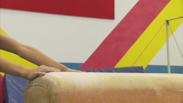 vídeos de stock, filmes e b-roll de interior shots of young boys practising pommel horse gymnastics skills on a practice horse without handles at a gymnasium at shichahai sports... - acrobata