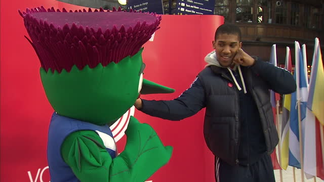 interior shots olympic 2012 gold medal winning heavy weight boxer anthony josua poses with the glasgow 2014 commonwealth games mascot thistleman for... - フォトコール点の映像素材/bロール