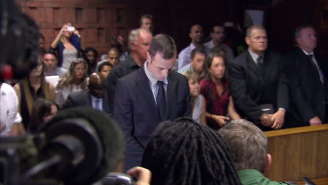 interior shots oscar pistorious olympic paralympic athlete standing in court room with his head down oscar pistorius in court at pretoria magistrates... - オスカー・ピストリウス点の映像素材/bロール