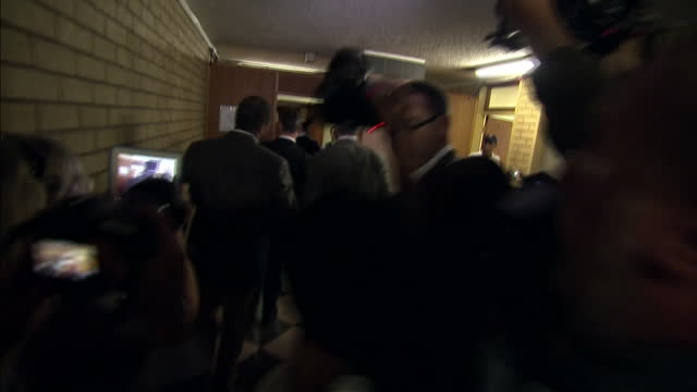 interior shots oscar pistorius walks to court room for first day of trial surrounded by media scrum on march 03 2014 in pretoria south africa - オスカー・ピストリウス点の映像素材/bロール