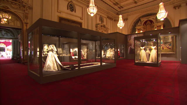 interior shots panning between various display cases in the queen's coronation exhibition at buckingham palace containing various outfits worn by... - buckingham palace stock-videos und b-roll-filmmaterial