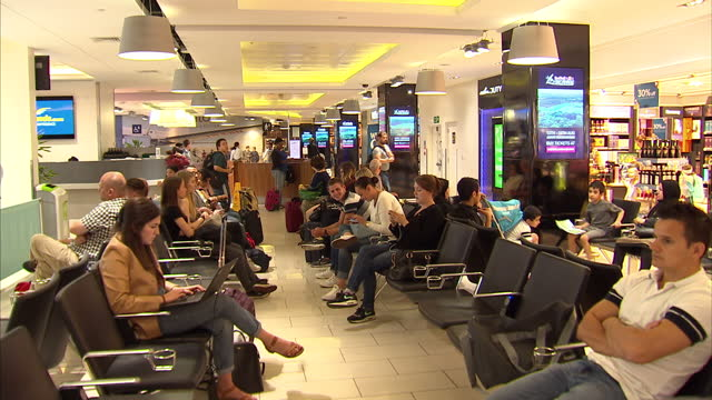 Interior shots passengers sitting around in seating areas at gates in London City Airport departures lounge waiting for flights on July 27 2016 in...