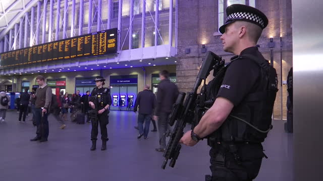 Interior shots passengers talking to police officers Interior shots armed police officers with guns standing guard and patrolling through King's...