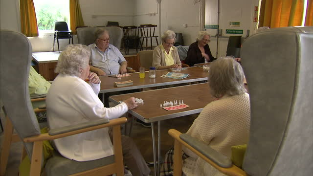 stockvideo's en b-roll-footage met interior shots pensioners playing bingo in day care centre interior shots old lady reading magazine by window vox pops interviews ella thomas age uk... - bingo