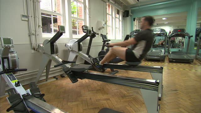 interior shots people exercising in the gym woman using suspension trainer men on crosstrainer rowing machine on september 02 2015 in london england - cross trainer stock videos and b-roll footage
