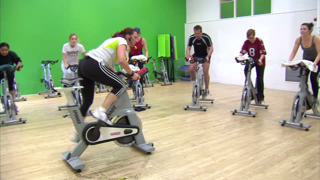 interior shots people on cycling machines in spinning class being orchestrated by a trainer in gym spinning cycling class in gym on july 19, 2012 in... - インドアサイクリング点の映像素材/bロール