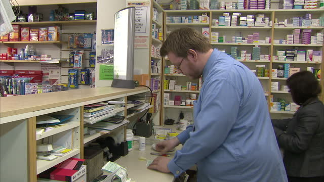 Interior shots pharmacist working on perscription order behind counter Pharmacist collecting prescription at pharmacy on March 11 2013 in Cambridge...