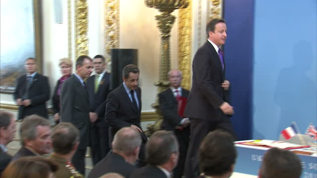 interior shots prime minister david cameron & french president nicolas sarkozy walk into press room in lancaster house & sit down at desk & sign the... - 50 seconds or greater stock videos & royalty-free footage