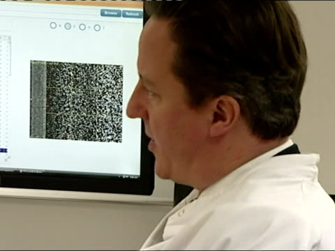 vídeos de stock, filmes e b-roll de interior shots prime minister david cameron wearing a white lab coat speaking to staff at dna laboratory at cancer research uk's cambridge research... - david cameron político