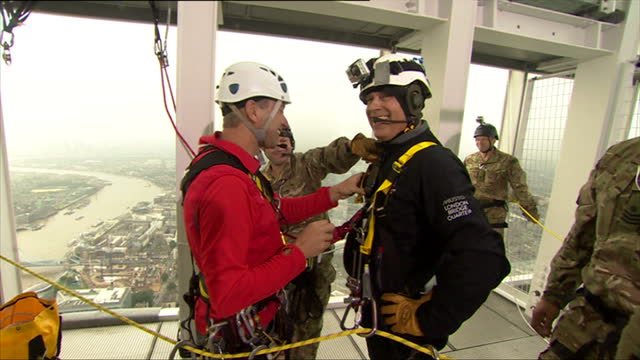 interior shots prince andrew abseils down shard tower & with the help of aides gets into section where he has his harnesses checked & prepares for... - abseiling stock videos & royalty-free footage
