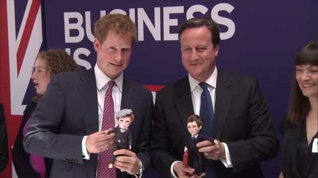 interior shots prince harry david cameron british prime minister are presented with 'lookalike' dolls making both men laugh prince harry grimace... - grimacing stock videos and b-roll footage