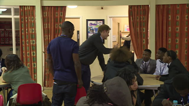 nottingham interior shots prince harry enters hall sits with group of teenagers at table and talks with them - contea di nottingham video stock e b–roll