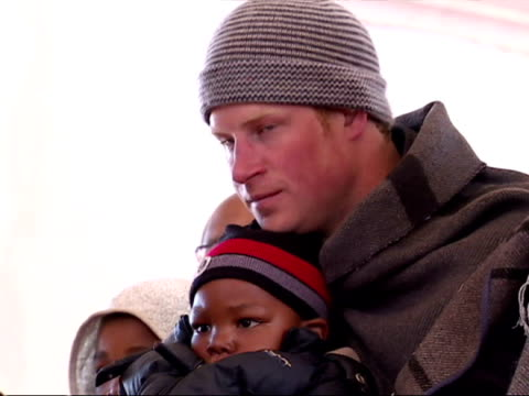 Interior shots Prince Harry Prince William listening to children singing Prince Harry has a child on his lap Prince Harry in Lesotho on June 17 2010...