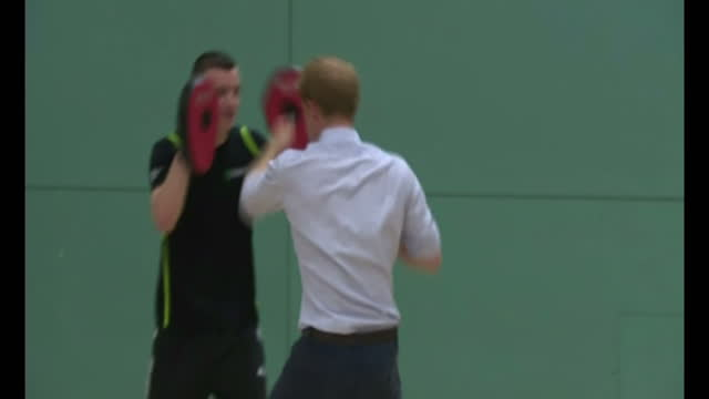 interior shots Prince Harry punching pads during boxing lesson