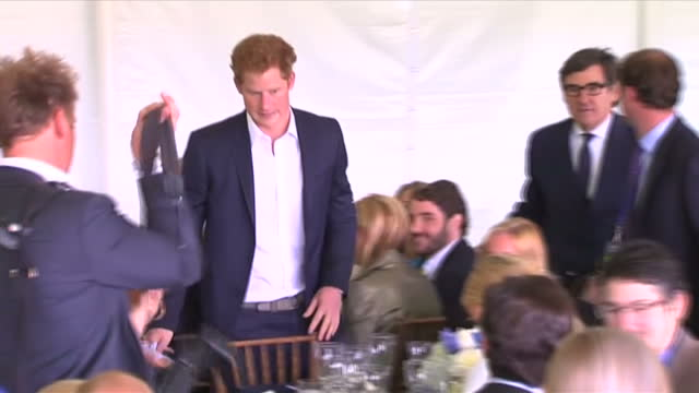 Interior shots Prince Harry receives a round of applause after finish his speech at the Sentebale Royal Salute Polo Cup sits down at dinner table...
