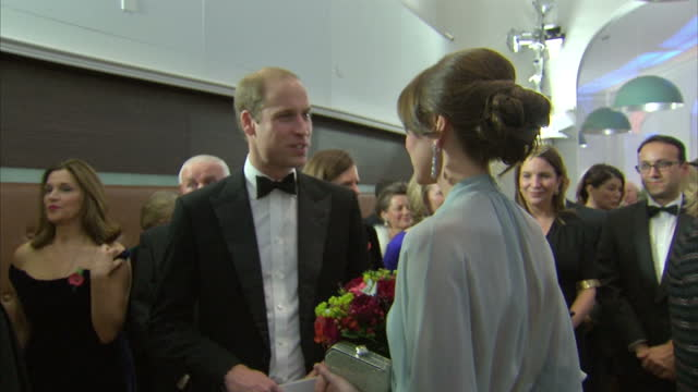 Interior shots Prince William Duke of Cambridge and Catherine Duchess of Cambridge finishing meet greet with Cast and leaving Daniel Craig kisses...
