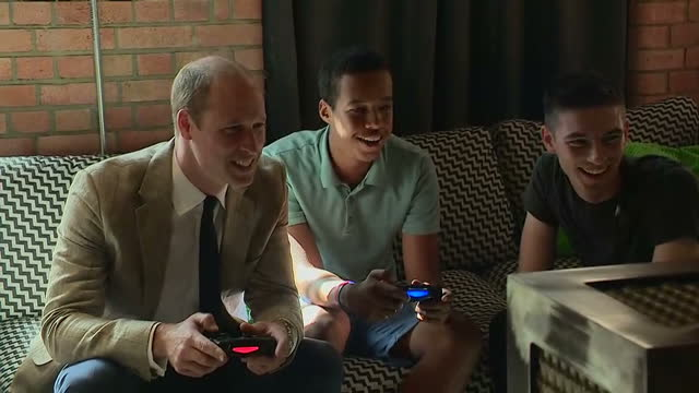 interior shots prince william duke of cambridge playing fifa video game on playstation console whilst on visit to youthscape at bute mills on august... - 公爵点の映像素材/bロール
