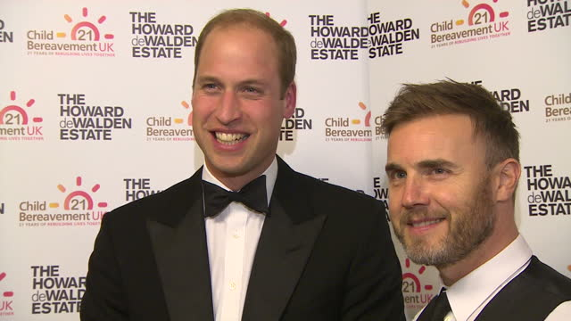 Interior shots Prince William Duke of Cambridge posing for photographs at the Child Bereavement UK 21st Birthday Dinner with Gary Barlow singer Julia...