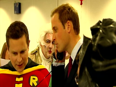 Interior shots Prince William speaks on telephone surrounded by people wearing fancy dress at a Prince's Trust charity project Prince William at...