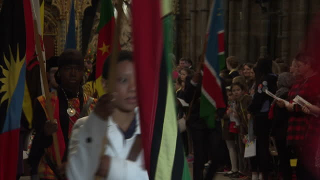 Interior shots procession underway with choir singing at Commonwealth Service on Commonwealth Day diverse range of flags from different Commonwealth...