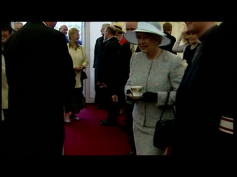 Interior shots Queen drinking a cup of tea and Prince Philip mingling in marquee Shows exterior shots crowds waiting on royal couple Northern Ireland...
